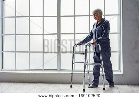 Smiling old woman in pajama holding foldable walker while standing in white corridor of clinic