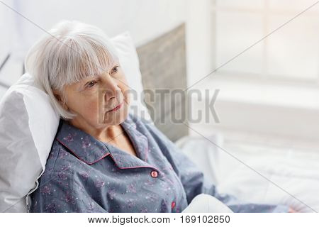 Unconcerned old woman is situating on soft bed near window in white hospital room