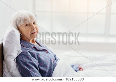 Calm retiree woman lying on white bed near window in apartment of clinic