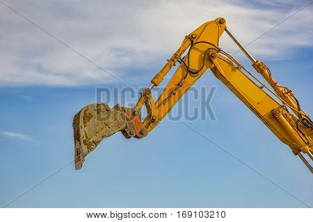 day view of single excavator boom arm with hydraulic Hoses and cylinder in action. Close