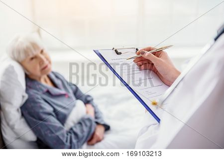 Therapeutic asking questions about health of old client while holding medical questionery tablet in clinic