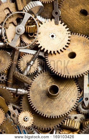 Aged gears cogwheels background. Retro mechanical clock accessories macro view. Shallow depth of field, soft focus.