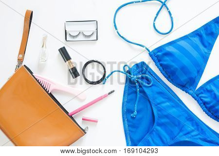 Flat lay of summer fashion with blue stripe bikini and girl accessories on white background