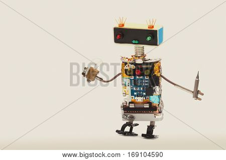 Serviceman robotic toy with lamp bulb and screwdriver. Fun kindly handyman worker, colorful head red blue light bulbs eyes. beige background. copy space