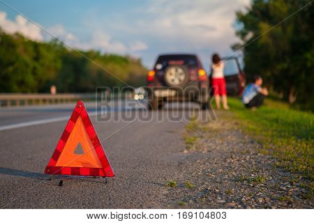 Close-up Of A Triangular Warning Sign. Couple Standing In Front Of Broken Down Car. Evening summer light. shallow depth of field, the focus is on the triangle