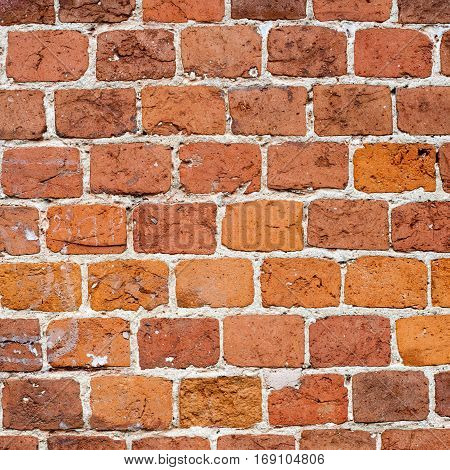 Aged red brick wall pattern photo. Vintage brickwork abstract object, white seam.