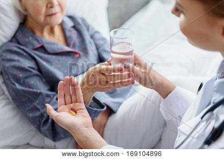 Doctor giving glass of water and covered medicine to retiree in clinic