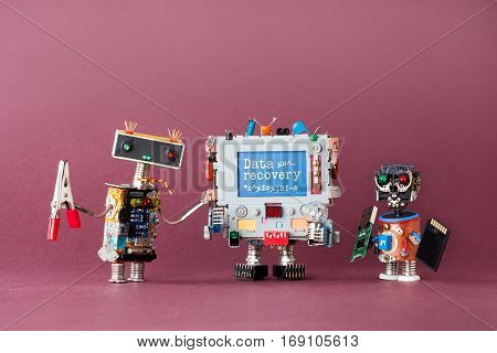 Data recovery concept. IT specialist robots and colorful computer warning text on blue display. Violet background, macro view photo