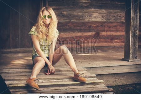 Trendy Hipster Model Girl Sitting on the Wooden Porch and Looking at Camera. Beautiful Street Style Fashion Woman in Sunglasses Outdoors. Toned and Filtered Photo with Copyspace. Wooden Background.