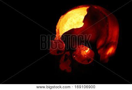 Burning skull - Old broken skull against black background with inner flame