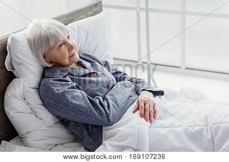 Smiling old woman is on glass-dropper while lying on soft white cot in hospital