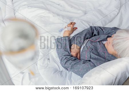 Unconcerned old woman is on glass-dropper while lying on soft white cot in hospital