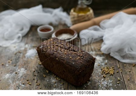 Close up view of fresh brown crispy loaf of bread lying on the wooden table sprinkled with flour.