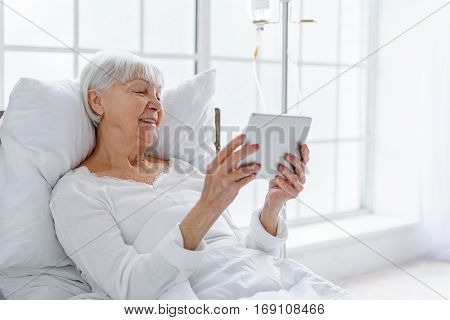 Happy senior woman using tablet while keeping and lying on bed in hospital