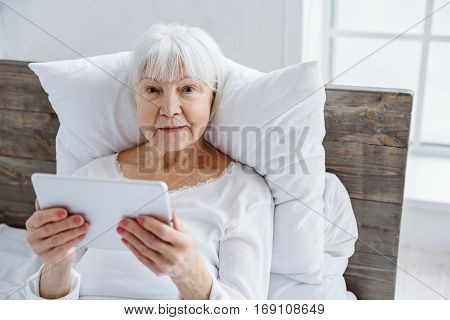 Outgoing old woman holding digital tablet in hand while staying in bed near window in polyclinic