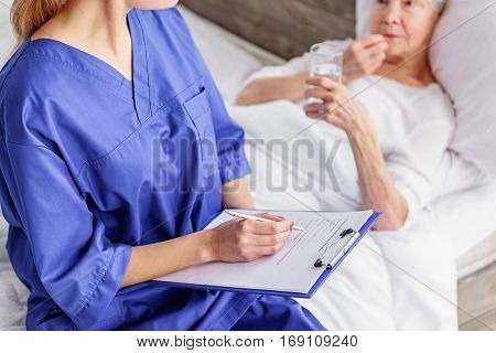 Doctor writing medical questioner tablet of old woman in hospital. Pensioner is drinking water while lying in soft bed in bright apartment