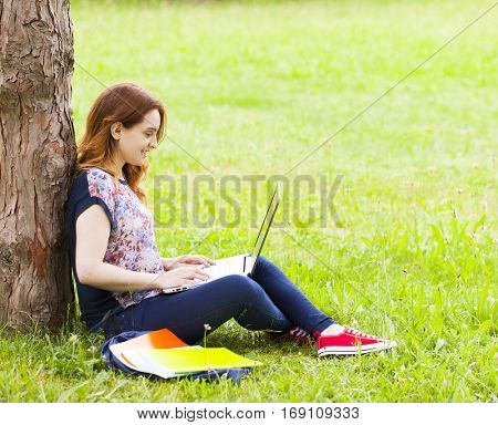Pretty student girl sitting on the grass and using laptop computer at the university campus