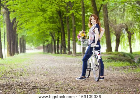 Smiling beautiful young woman standing with a vintage bicycle at the park
