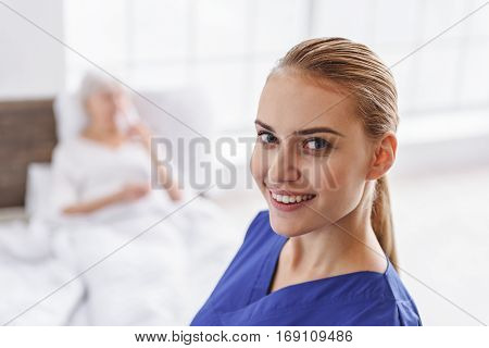 Focus on smiling attractive female doctor standing in hospital room of old woman