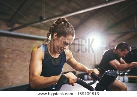 People Working Hard On Exercycle In Gym