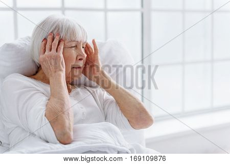 Distressed grandmother holding her head by hands while staying in bed