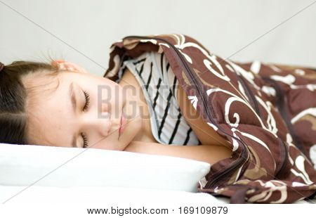 Little girl is sleeping in bed with her book and glasses