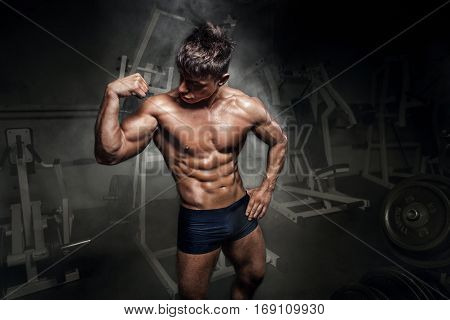 Bodybuilder man showing his biceps in gym