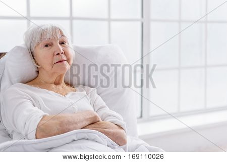 Composed old woman lying sick in comfortable cot in hospital apartment
