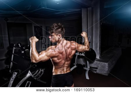 Bodybuilder stong man posing in the gym