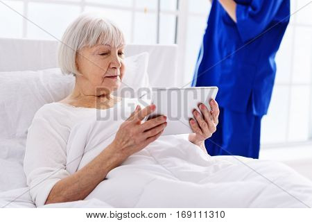 Outgoing old woman looking at digital tablet while lying in cosy white bed in polyclinic