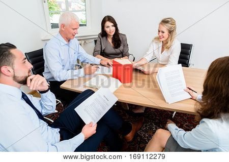 Lawyers in law firm reading documents and agreements at large conference table