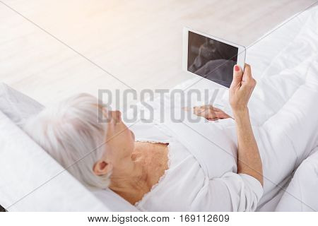 Calm grandmother looking at X-ray in digital tablet while holding it in hand
