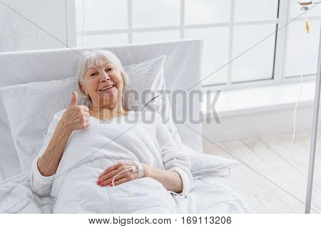 Smiling pensioner is on drip while lying on cot in room of clinic. She is giving thumb up