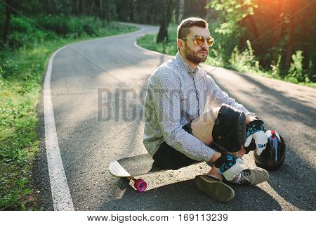 Skater Boy Sitting On His Longboard In Nature Park
