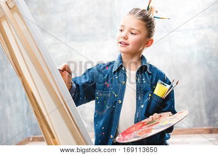 Little female artist holding palette and painting picture on easel