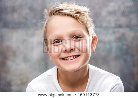 Close-up portrait of cute little boy smiling at camera