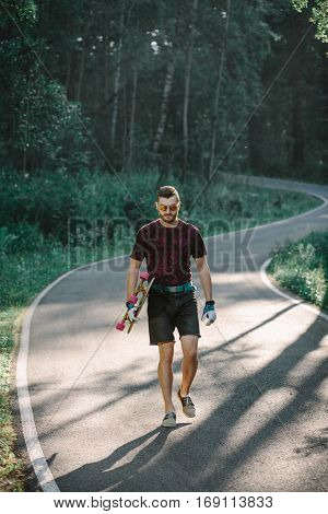 Young Man With Longboard On  Road In The Forest