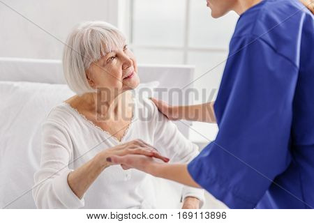 Young doctor describing state of health of old patient in hospital room. Outgoing pensioner listening therapeutic while sitting on soft bed