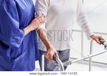 Practitioner learning pensioner going with gutter frame in hospital room