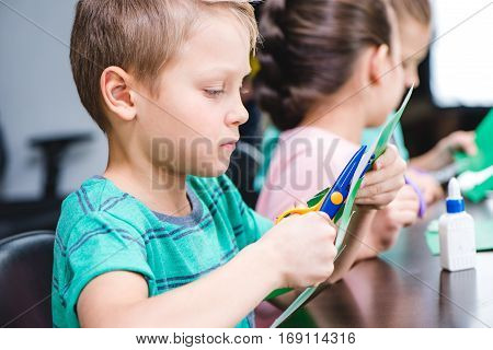 Schoolchildren making applique with colorful paper and scissors in school