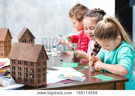 Schoolchildren making applique with colorful paper glue and scissors