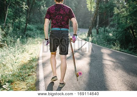 Young Man With Longboard Is Back On  Road In The Forest