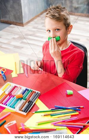 Schoolchild playing with plasticine and looking at camera