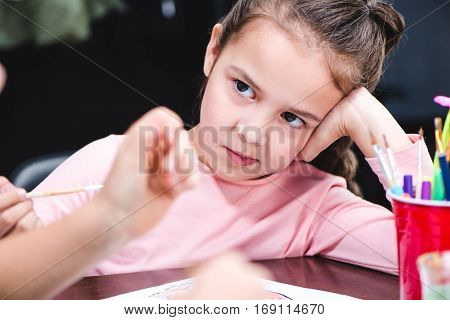 Close-up portrait of bored schoolchild sitting at table and looking away