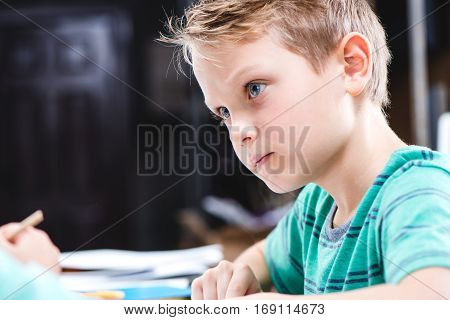 Close-up portrait of concentrated schoolchild sitting at table and studying
