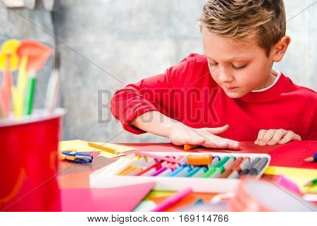 Concentrated schoolchild sitting at table and playing with plasticine