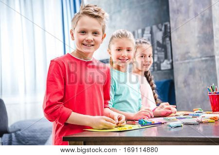 Schoolchildren playing with colorful plasticine and looking at camera