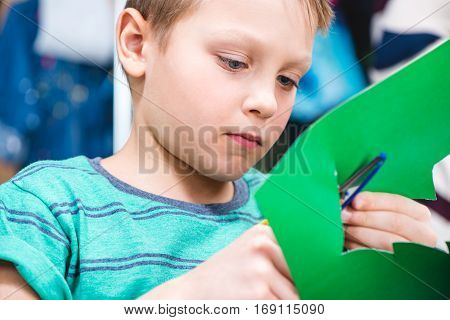 Close-up portrait of schoolchild cutting green paper with scissors
