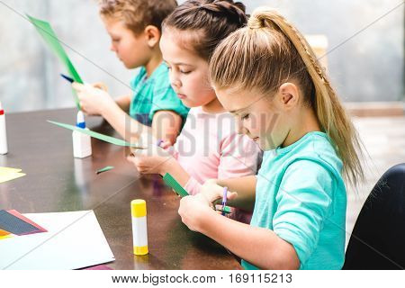 Schoolchildren sitting at table and making applique