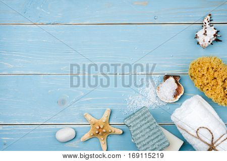 Spa and beach products on blue wooden planks with copyspace